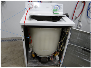 Photograph 1: Location of the pressure switch, tubing, and drain pump on a washing machine.